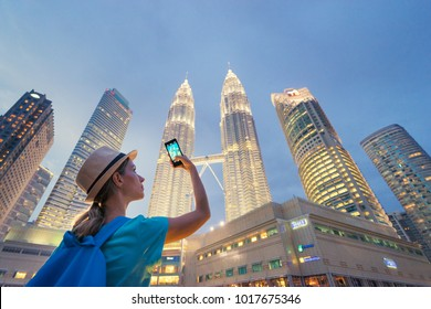 Travel and technology. Young  woman taking photo with her smartphone of Petronas Twins Towers in Kuala-Lumpur at evening, Malaysia, 23 November 2015.