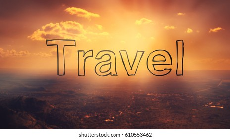 """Travel"" text on beautiful sunset background. View from the top of a mountain. Warm colors and bright sunlight."