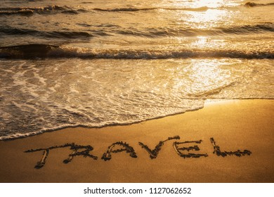 Travel text written in the sand during sunset over the ocean. Travel concept.
