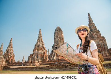 Travel Thailand Ayutthaya tourist woman on Asia sightseeing holding map with big pagoda and spectacular buddhist attraction in Wat Chaiwatthanaram. Tourism people concept with mixed race Asian girl.