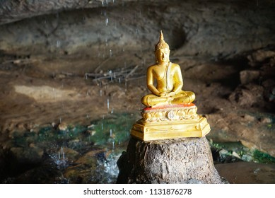 Travel Thailand - Buddha statue in Tham Kra Sae With drops rain as a background at the River Kwai Karnchanaburi, Thailand, Space for text in template.