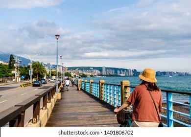 Travel therapy concept : traveler enjoy biking along the sea bridge at Tamsui fisherman's wharf area , Taiwan Tamsui  10 May 2019