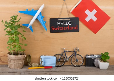"Travel time - blackboard with text ""Love switzerland"", flag of the switzerland, airplane model, camera, bicycle on brown wooden background"