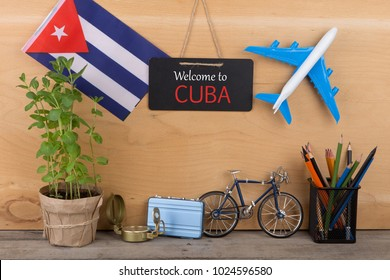 "Travel time - blackboard with text ""Welcome to Cuba"", flag of the Cuba, airplane model, camera, bicycle on brown wooden background"