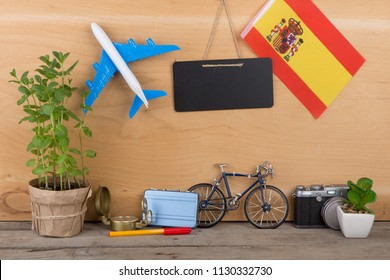 Travel time - blank blackboard, flag of the Spain, airplane model, camera, bicycle on brown wooden background