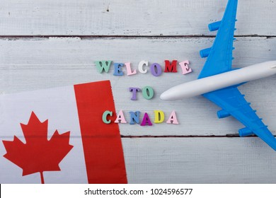 "Travel time - colorful wooden letters with text ""Welcome to Canada"" , flag of the Canada, airplane model, passport on white wooden background"