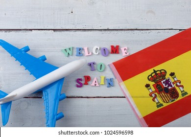 "Travel time - colorful wooden letters with text ""Welcome to Spain"" , flag of the Spain, airplane model, passport on white wooden background"