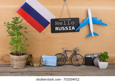 "Travel time concept - blackboard with text ""Hello Russia"", flag of the Russia, camera, airplane model, little bicycle and suitcase, compass on wooden background"