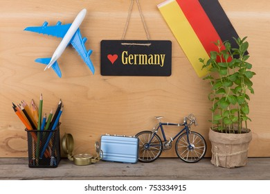 "Travel time concept - blackboard with text ""Love Germany"", flag of the Germany, airplane model, little bicycle and suitcase, compass on wooden background"