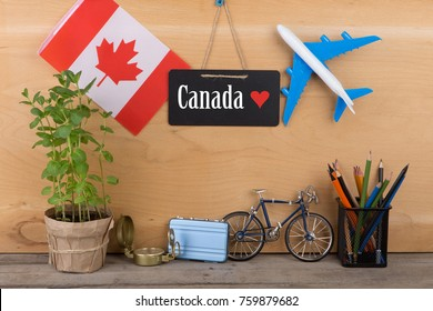 "Travel time concept - blackboard with text ""Canada love"", flag of the Canada, airplane model, little bicycle and suitcase, compass on wooden background"