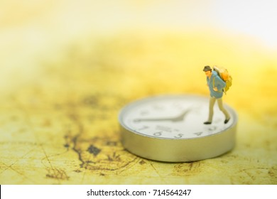 Travel and time concept. Traveler miniature people figure walking on watch and on world map.