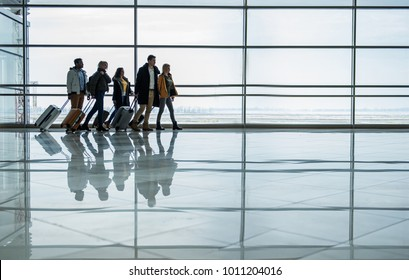 Travel together. Full length of pleasant young men and women are walking along terminal hall with luggage to departure area. Big window in background. Copy space in the right side