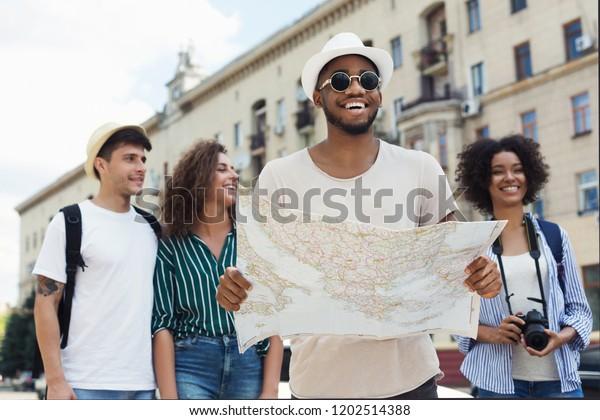Voyagez ensemble. Des hipsters heureux utilisant la carte de navigation pour explorer la ville