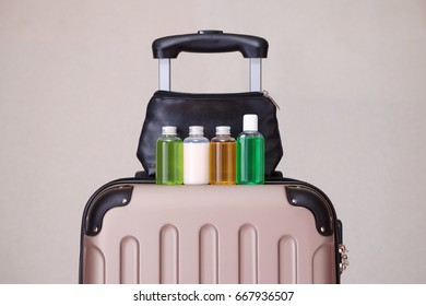 travel toiletries, small plastic bottles of hygiene products on the suitcase and cosmetic bag