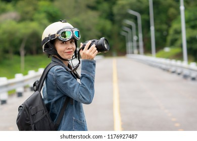 Travel touris concept, Asian tourist holding camera to travel and  take photo of beautiful nature, Cute girl holding bagplack and wearing helmet on road street.  Freedom journey of pretty Asian girl.