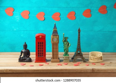 Travel and tourism background with souvenirs from around the world on wooden table. Romantic valentine's day trip concept.