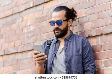 travel, tourism, communication, technology and people concept - man with backpack texting on smartphone on city street