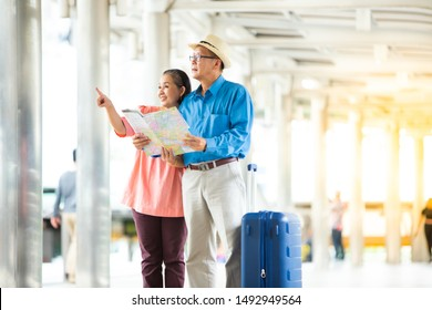 Travel and tourism concept. Happy Senior couple woman and man traveling together looking for destination with city map