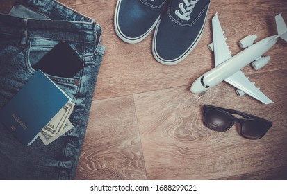 Travel or tourism concept. Jeans, hundred dollar bills, sneakers, smartphone, passport, sunglasses, airplane on a wooden floor. Top view. Flat lay