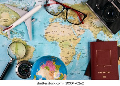 Travel and tourism concept with passport travel documents photo camera compass airplane on world map background with copy space, top view.