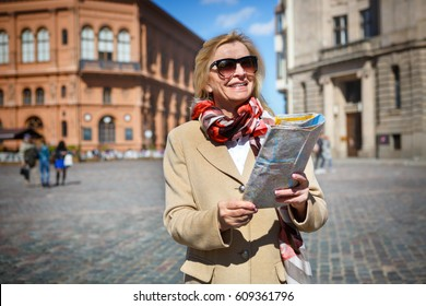 Travel and tourism concept. Smile Old senior woman of backpackers with sunglasses, holding in hands travel map and walking by old european town street. Spring sunny time