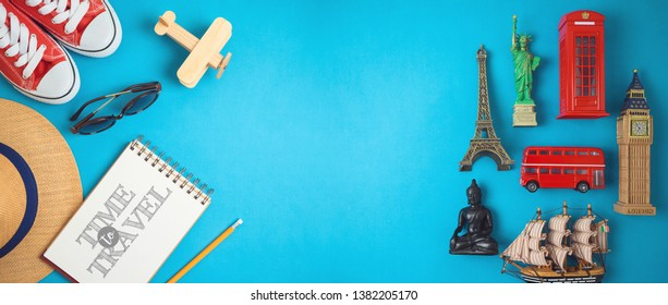 Travel and tourism concept with traveling accessories and souvenirs from around the world on blue background. Top view from above