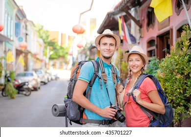 Travel and tourism. Couple of backpackers walking together on asian street.