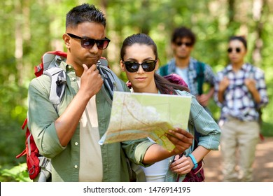travel, tourism, hike and people concept - group of friends with map and backpacks in forest