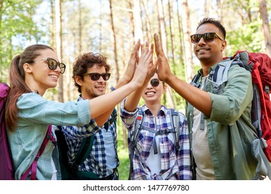 travel, tourism, hike and people concept - group of friends with backpacks talking and making high five in forest