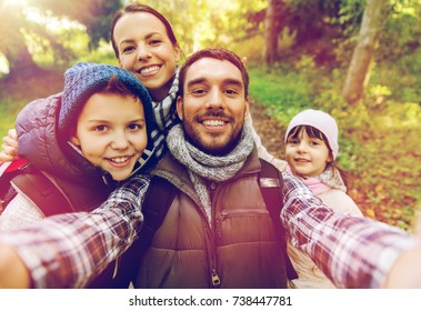 travel, tourism, hike and people concept - happy family with backpacks taking selfie and hiking