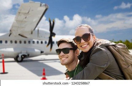 travel, tourism and people concept - couple of tourists with backpacks over plane on airfield background