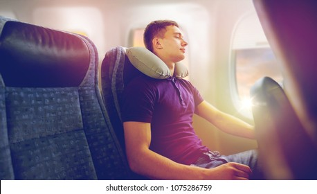 travel, tourism and people concept - happy young man sleeping in plane with inflatable pillow over porthole background