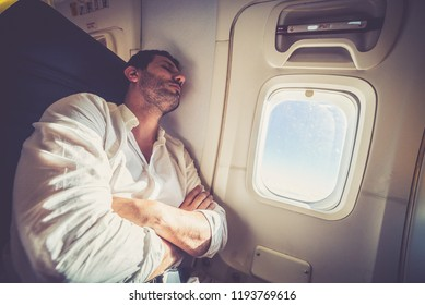 travel, tourism and people concept - happy young man sleeping in plane over porthole background