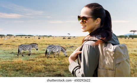 travel, tourism and people concept - happy young woman with backpack over african savannah and zebras background