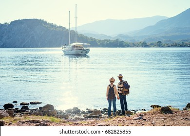 Travel and tourism. Senior family couple standing together on Mediterranean sea beach.
