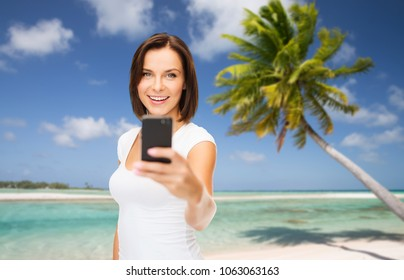 travel, tourism, summer holidays and vacation concept - happy young woman taking selfie by smartphone over exotic tropical beach with palm tree background