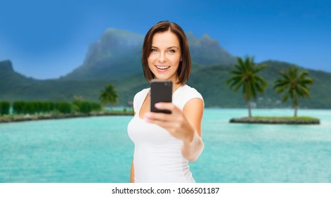 travel, tourism, summer holidays and vacation concept - happy young woman taking selfie by smartphone at touristic resort over bora bora island beach background