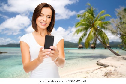 travel, tourism, summer holidays and vacation concept - happy young woman taking selfie by smartphone over exotic tropical beach with palm tree and bungalow sheds background