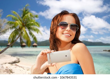 travel, tourism, summer holidays and vacation concept - happy young woman taking selfie by smartphone over exotic tropical beach with bungalow sheds background in french polynesia