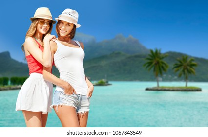 travel, tourism, summer holidays and vacation concept - smiling young women in hats at touristic resort over exotic bora bora island beach background
