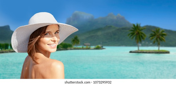 travel, tourism, summer holidays and vacation concept - happy young woman in sun hat at touristic resort over bora bora island beach background