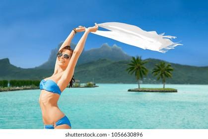travel, tourism and summer vacation concept - woman in bikini and sunglasses at touristic resort over bora bora island beach background