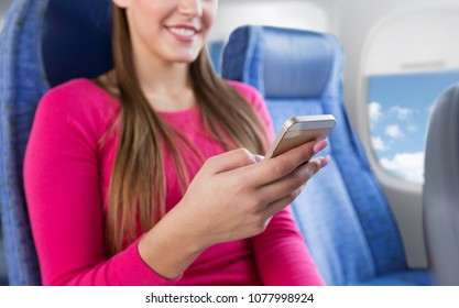 travel, tourism, technology and air flights concept - close up of happy young woman sitting in plane with smartphone over porthole background