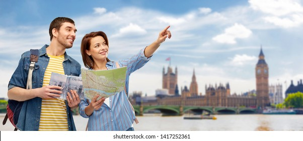 travel, tourism and vacation concept - happy couple of tourists with city guide, map and backpacks over london city background