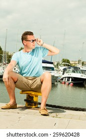 Travel tourism vacation and people concept. Fashion portrait of handsome man on pier against white yachts in port