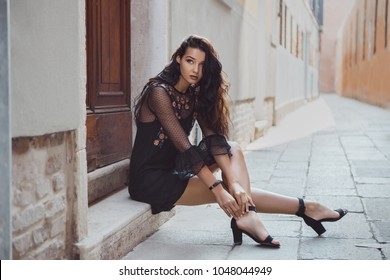 Travel tourist girl on vacation posing on city street with beautiful legs in high heel shoes. Attractive young romantic passion woman sitting on sidewalk against beautiful view on venetian quiet