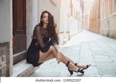 Travel tourist girl on vacation posing on city street. Attractive young romantic passion woman sitting on sidewalk against beautiful view on venetian quiet street in Venice, Italy. Gorgeous mixed race