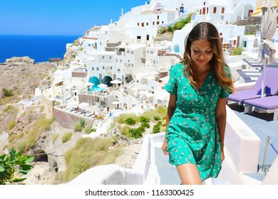 Travel tourist happy woman climbs the stairs in Santorini, Cyclades Islands, Greece, Europe. Girl on summer vacation visiting famous tourist destination having fun smiling in Oia.