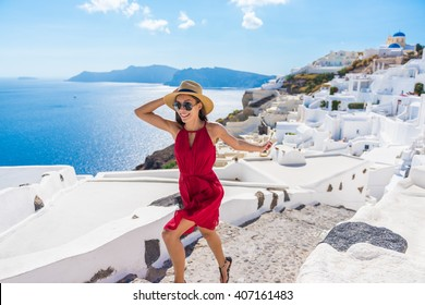 Travel Tourist Happy Woman Running Stairs Santorini, Greek Islands, Greece, Europe. Girl on summer vacation visiting famous tourist destination having fun smiling in Oia.