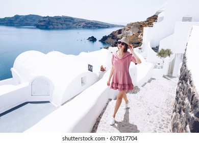 Travel Tourist Happy Woman waking Stairs Santorini, Greek Islands, Greece, Europe. Girl on summer vacation visiting famous tourist destination having fun smiling in Oia.